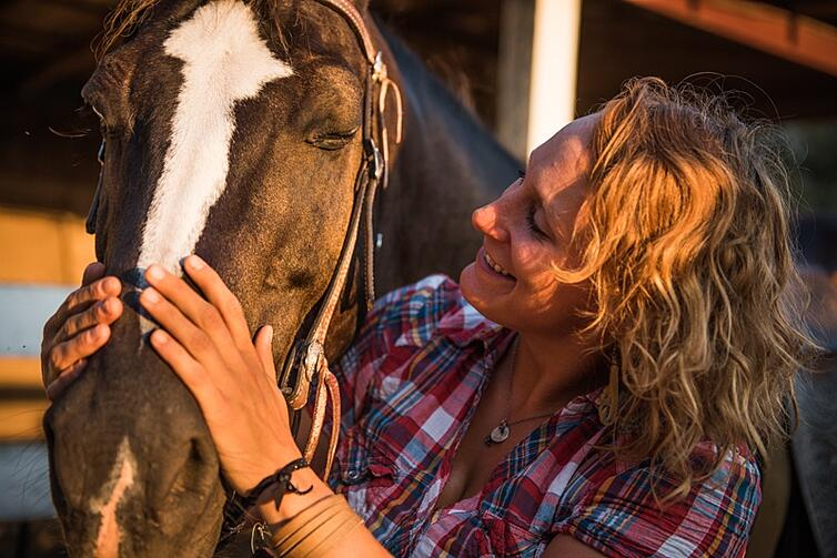Jamie pets gabe a guarter horse she leads trail rides with on the farm at sunset.jpg