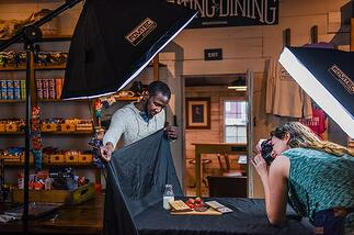 Chad Hunter assisting in a product photo shoot for a locally sourced item in the general store