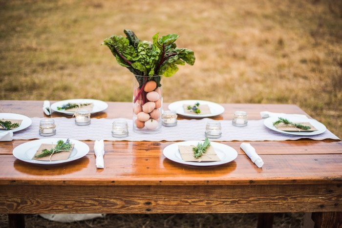 Farm to table display with swiss chard and eggs. Glass vase and place settings with rosemary and lavander tied to menu