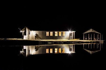 Pond house reflecting on the water at night