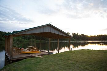 Kayaks a dock with swing benches and a picnic table are available.