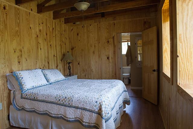 Pond house room 1 with full bed and country quilt agrotourism lodging option.