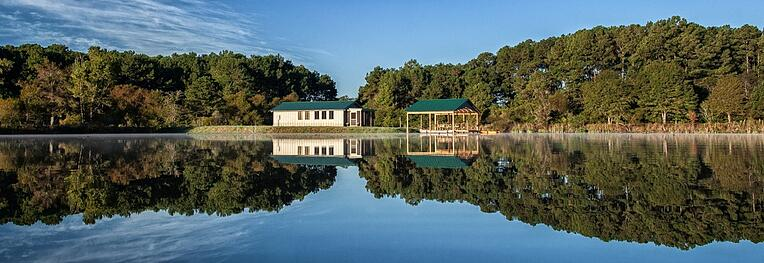 Pond House reflecting in pond water on a sunny day for agroutourism lodging.