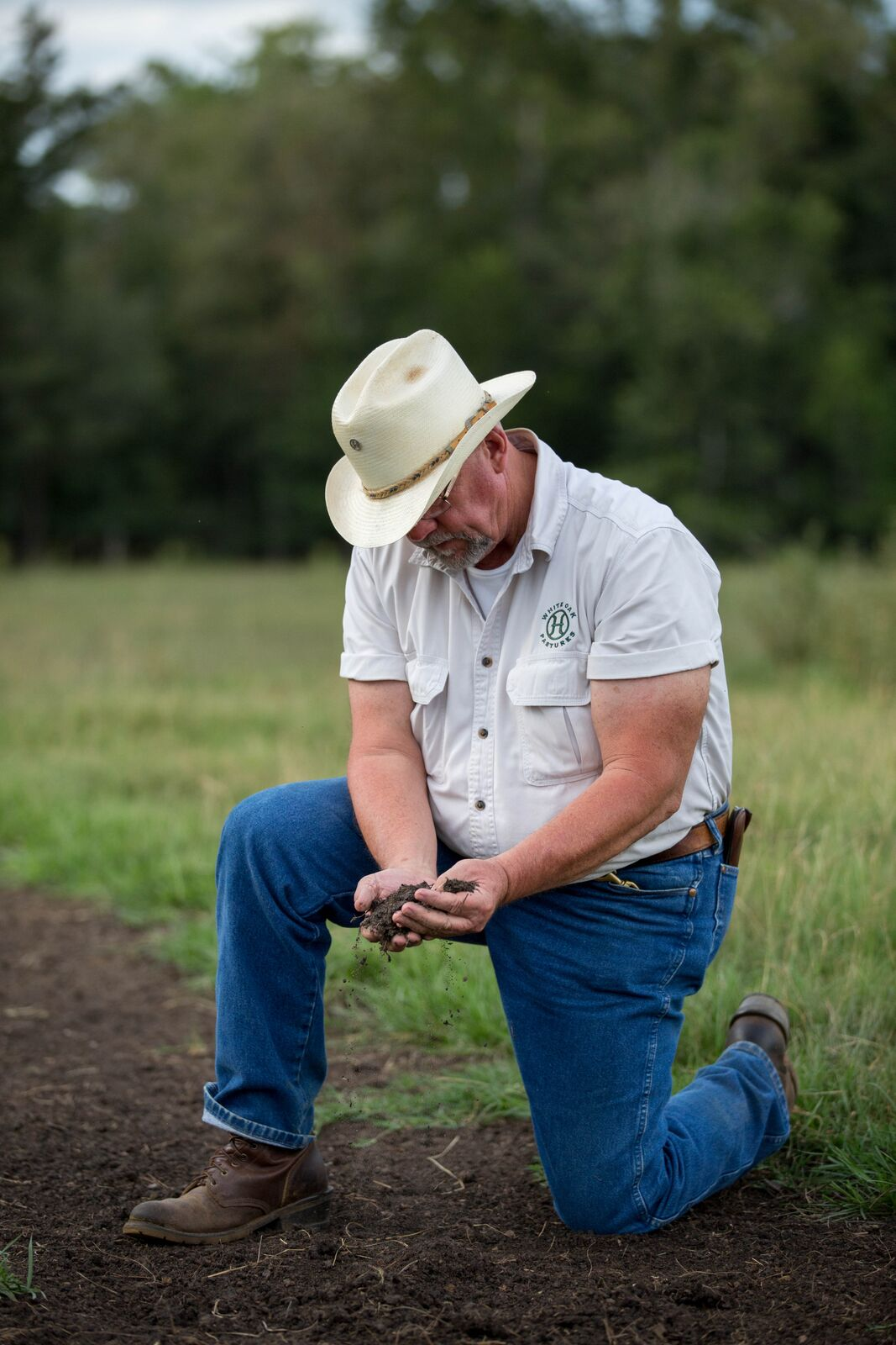 Will Harris examines the soil at White Oak Pastures