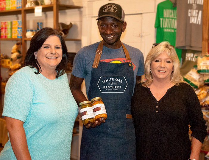 Chad poses with LeAnns founders when they visited White Oak Pastures Chad sourced their product for the General Store
