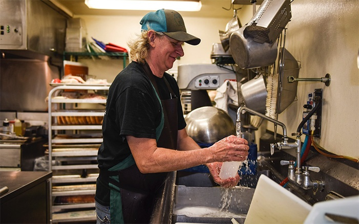 cecil washing dishes at the farm to table dining Pavillon at white oak pastures.jpg